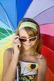 Teenage girl outdoors. Girl in sunglasses on background of iridescent umbrella. Slim teenage girl looking at camera on top of tinted sunglasses smiling Royalty Free Stock Images