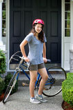 Teenage girl outdoors resting on her bicycle while in front of h Stock Image
