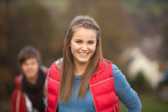 Teenage Girl Outside With Boyfriend In Background. Smiling at camera Royalty Free Stock Images