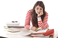 Teenage girl overwhelmed by homework. Teenage girl feeling stressed, overwhelmed by piles of school work on foreground table. Red and white striped shirt, white Stock Photography
