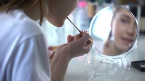 Teenage girl painting lips with gloss, desire to be beautiful, daily make-up stock footage