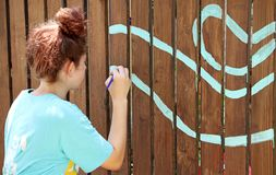 A teenage girl paints with a brush on a brown fence. A teenage girl paints with a brush on a wooden brown fence, turquoise drawing Royalty Free Stock Image