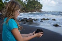 Teenage girl with palms full of volcanic black lava sand Stock Photos