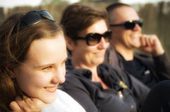 Teenage girl with parents. A cute smiling girl wearing sunglasses with parents in the background stock photos