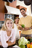 Teenage girl with parents in kitchen smiling Stock Photo
