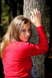 Teenage Girl in the Park. A teenage girl standing against a tree in the park Royalty Free Stock Image
