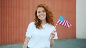 Teenage girl patriot holding US flag outdoors smiling looking at camera. Teenage girl young patriot is holding national US flag outdoors smiling looking at stock footage