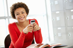 Teenage girl with phone in class Stock Image
