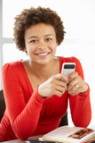 Teenage girl with phone in class Royalty Free Stock Image