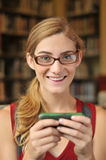 Teenage girl on phone texting in library Stock Images