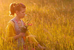 Teenage girl picking flowers at sunset. Cute teenage girl picking flowers on the meadow on sunny spring day Royalty Free Stock Photo