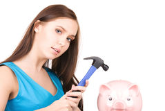 Teenage girl with piggy bank and hammer Royalty Free Stock Photo
