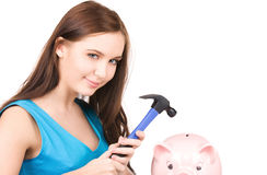 Teenage girl with piggy bank and hammer Stock Photography