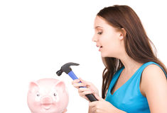 Teenage girl with piggy bank and hammer Stock Photos