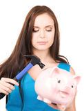 Teenage girl with piggy bank and hammer Royalty Free Stock Image