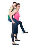 Teenage girl piggybacks her friend Stock Images