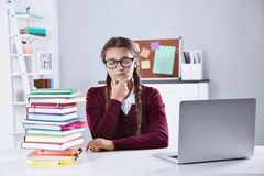 Teenage girl with pile of books and laptop sitting at  desk in a classroom Royalty Free Stock Image