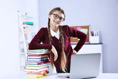Teenage girl with pile of books and laptop standing at  desk in a classroom Royalty Free Stock Photo
