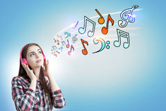 Teenage girl with pink headphones, notes, blue Stock Photos