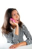 Teenage girl on pink phone listening at desk Stock Photography