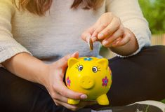 Teenage girl places coin into piggy bank to save for the future. Teenager places coin into piggy bank to save for the future Royalty Free Stock Image