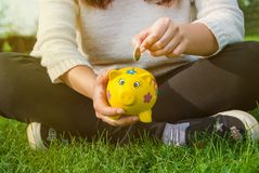 Teenage girl places coin into piggy bank to save for the future. Teenager places coin into piggy bank to save for the future Stock Photos