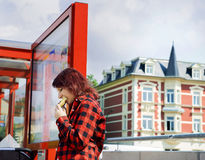 Teenage girl in a plaid shirt listening to music while waiting for a bus Royalty Free Stock Images