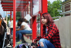 Teenage girl in a plaid shirt listening to music while waiting for a bus Royalty Free Stock Image