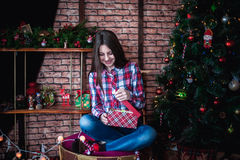 Teenage girl in a plaid shirt opens box Christmas gift Royalty Free Stock Image