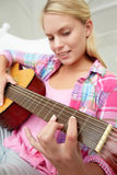 Teenage girl playing acoustic guitar. Focusing stock images