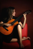 Teenage girl playing an acoustic guitar Royalty Free Stock Image