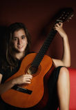 Teenage girl playing an acoustic guitar Royalty Free Stock Images