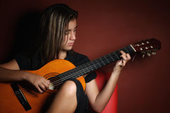 Teenage girl playing an acoustic guitar Stock Images