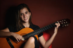 Teenage girl playing an acoustic guitar Royalty Free Stock Photo