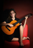 Teenage girl playing an acoustic guitar Royalty Free Stock Photography