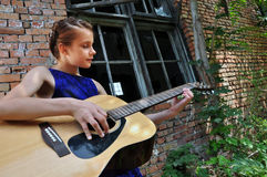 Teenage girl playing acoustic guitar in the street Royalty Free Stock Image