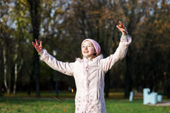 Teenage girl playing with autumnal leaves Royalty Free Stock Photography