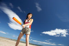 Teenage girl playing baseball on beach Stock Images