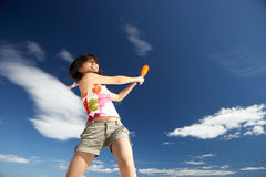 Teenage girl playing baseball on beach Stock Photography