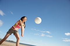 Teenage girl playing beach volleyball Stock Image
