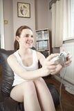 Teenage girl playing on a console game. Front view of a young teenage girl playing on a console game. happy smiling girl playing in her home Royalty Free Stock Photography