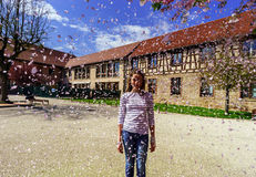 Teenage girl playing with falling petals on the sun Royalty Free Stock Photos