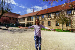 Teenage girl playing with falling petals on the sun. France royalty free stock image