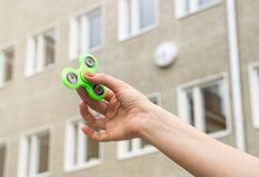 Teenage girl playing with fidget spinner. At recess or break in school yard Royalty Free Stock Image