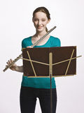 Teenage girl playing flute Stock Images