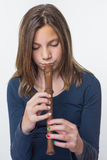 Teenage girl playing the flute. Young caucasian teenage girl playing the flute isolated on grey white background Stock Photo