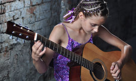 Teenage girl playing guitar Stock Images