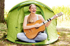 Teenage girl playing on guitar near the tent Stock Photos