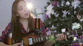 The teenage girl playing guitar, singing a sad song near christmas tree. Happy new year and merry christmas concept. Hard rock and rock and roll stock video footage