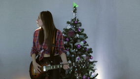 The teenage girl playing guitar, singing song and dancing near christmas tree. Happy new year and merry christmas concept. Hard rock and rock and roll stock video